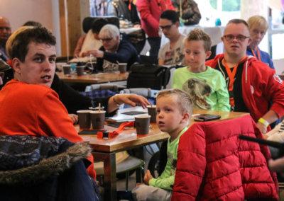 Jongeman en klein jongetje aan tafel die achterom kijken tijdens het jubileumfeest