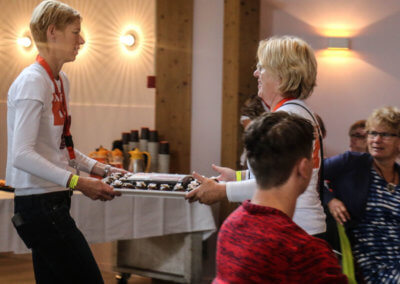 2 medewerkers van KansPlus overhandigen de taart aan elkaar voor het jubileumfeest