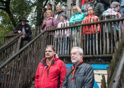 2 mensen met een oranje sleutelhanger om die staan te kijken naar de dieren