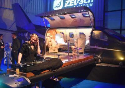 Een vrouwelijke DJ staat muziek te draaien vanaf een vliegtuigvleugel tijdens een evenement