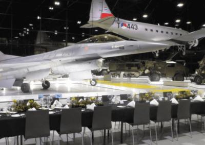 Tafels met zwarte bekleding in de zaal met een F15 straaljager ervoor en een vliegtuig aan het plafond