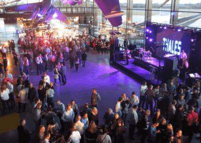 Mensen staan in een halve cirkel tijdens een bedrijfsfeest en een live band speelt muziek op een podium