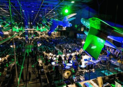 Verschillende muziekorkesten die muziek maken. Gevechtsvliegtuigen die aan het plafond hangen en publiek wat toekijkt.