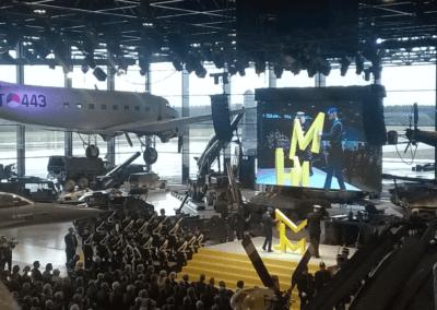 De opening van het Nationaal Militair Museum tussen tanks en vliegtuigen met een grote groep militairen die staan en een zaal vol mensen die in een stoel zitten