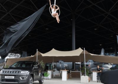 Een nieuwe Jeep word onthuld door een trapeze artieste die in een hoepel aan het dak hangt