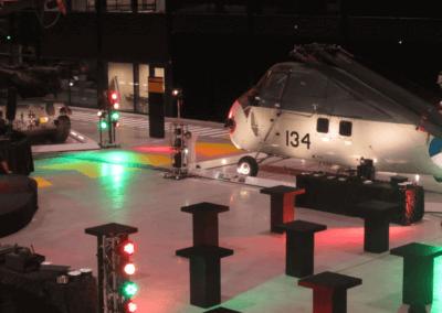 Zwarte statafels in een grote hal met een Sikorsky helicopter en discoverlichting