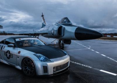 Een sportwagen en een gevechtsvliegtuig naast elkaar op de startbaan tijdens een productlancering