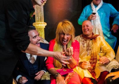 Illusionist doet een truc met een ring om de pink bij een vrouw die heel hard moet schreeuwen. Naast haar zitten 2 mannen op hun stoel hard te lachen