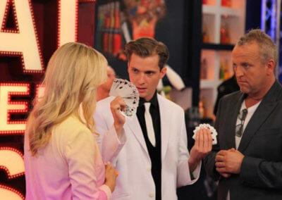 Illusionist Andrew Melia tijdens de TV show Beat the Best laat tijdens een van zijn acts kaarten zien aan Gordon en Wendy van Dijk
